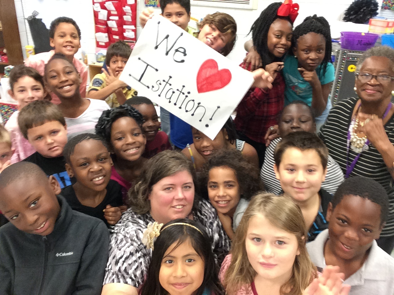 """Students and teacher holding a """"We love Istation"""" poster"""